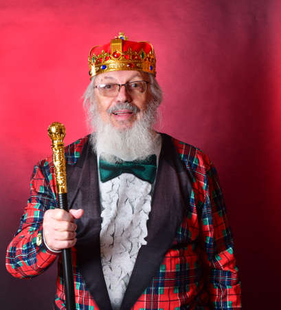 Old gentleman in fake tuxedo, red crown indulging is being a egoist, lover of self, selfish and conceited. Old Caucasian man in faux tuxedo, crown and gold tipped baton, showing self love and conceit. Banco de Imagens