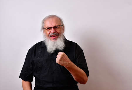 Angry old man makes a threatening gesture with his fist.  Mature gentleman with a  black guayabera shirt and long white beard.