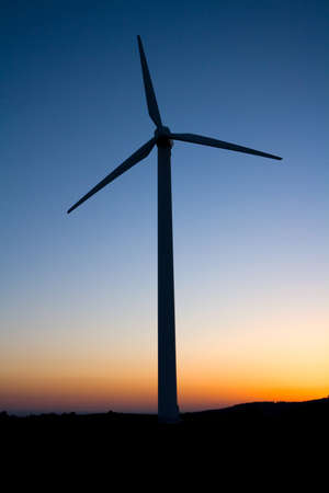 wind turbine at sunset with red and blue sky photo