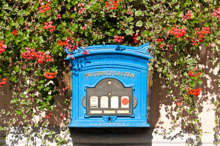 importantly: old german mail box at a flower wall