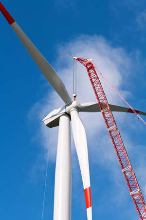 Wind turbine under construction with a crane photo