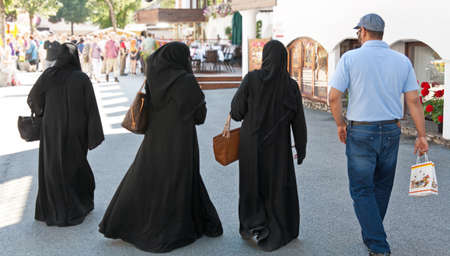 veiled: Veiled women while shopping in a pedestrian zone