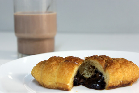 A chocolate croissant open on a plate, with a glass of milk in the background.