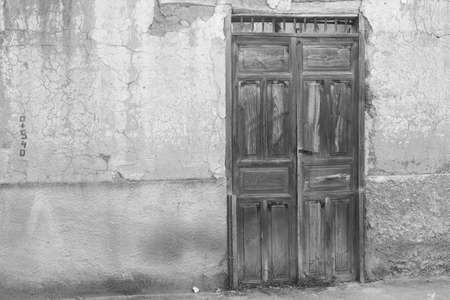 loja: Black and white, old weathered wooden door in southern ecuador Stock Photo