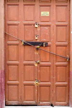 loja: 8 locks on an old brwon door, Loja Ecuador   editorial