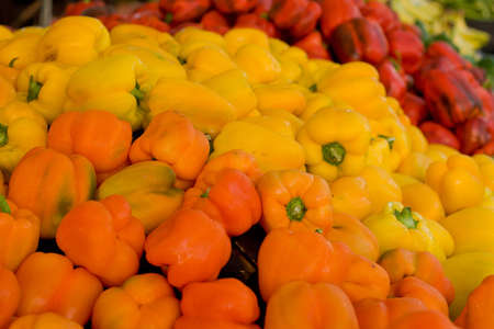 Orange, yellow and red peppers displayed for sale at farmers market  yellow dominate,orange and red soft focus