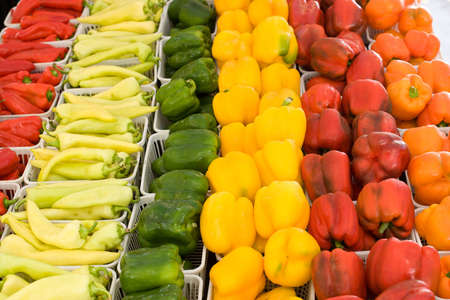 Orange, yellow,green and red peppers displayed for sale at farmers market  yellow dominate,orange and red soft focus Stock Photo