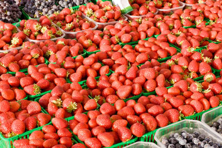 Fresh Strawberrys on display and for sale at farmers market with grapes in foreground and background  Stock Photo