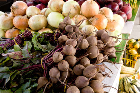 Fresh raw beets on display and sale at farmers market, with onions softfocus in background  beetroot Stock Photo