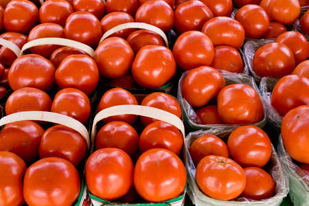 Fresh red ripe tomatoes on display and sale at farmers market, in baskets Stock Photo