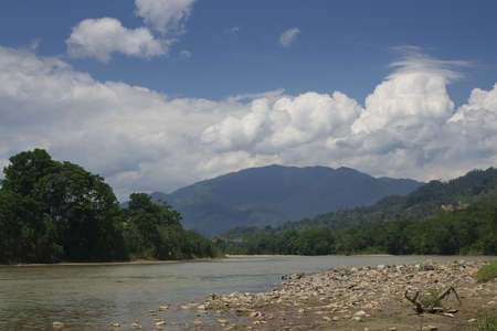loja: The Zamora river with the Andes mountains as it flows towards the amazon gravel and rocks in front  Stock Photo
