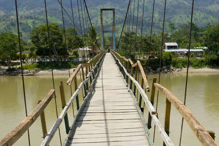 An old wooden suspesion bridge crossing a river in the amazon region, Ecuador