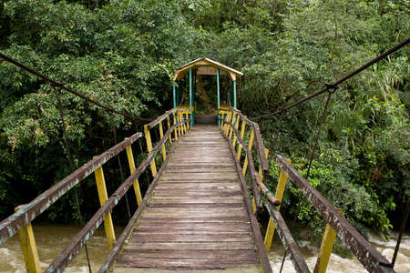 Pedestrian suspension bridge over river in rainforest Stock Photo - 17152084