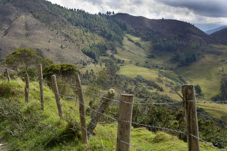 cattle wire: Barbed wire fence in the serria of ecuador with andes mountains in background
