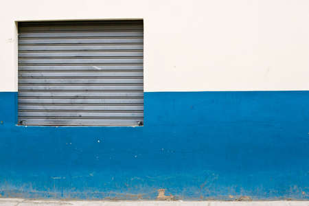 Closed after-hours store front in Latin-Americian downtown, blue and white wall roller steal shutters Stock Photo - 17334805