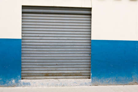 Closed after-hours store front in Latin-Americian downtown, blue and white wall roller steal shutters