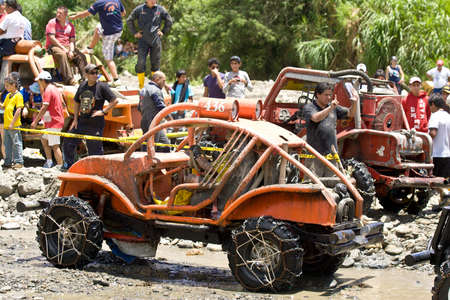 loja: MALACATOES LOJA ECUADOR FEB 10 2013. Custom 4X4 race on riverside Malacatoes Southern Ecuador Feb 10 2013. Town names are painted on the raders.