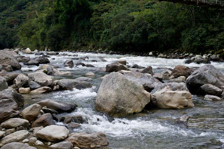 swiftly: Water swiftly flowing around rock in a river in the Andes Mountains