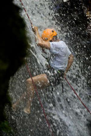 ZAMORA REGION, YANTZAZA, ECUADOR-May 11:Rappel student climbs down waterfall  in Yantzaza, Ecuador on May 11, 2013. Rappelling is part of a tourism class. Editorial