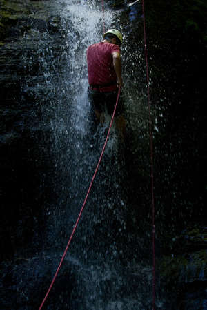 rappelling: ZAMORA REGION, YANTZAZA, ECUADOR-May 11:Rappel student climbs down waterfall  in Yantzaza, Ecuador on May 11, 2013. Rappelling is part of a tourism class. Editorial