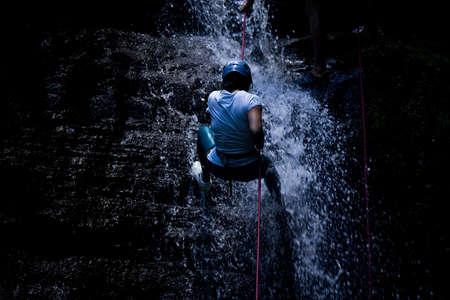 ZAMORA REGION, YANTZAZA, ECUADOR-May 11:Rappel student climbs down waterfall  in Yantzaza, Ecuador on May 11, 2013. Rappelling is part of a tourism class.