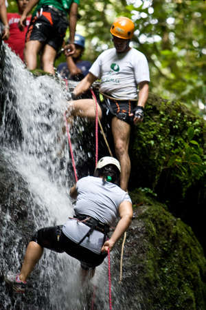 ZAMORA REGION, YANTZAZA, ECUADOR-May 11:Rappel student climbs down waterfall guided by instructors in Yantzaza, Ecuador on May 11, 2013. Rappelling is part of a tourism class.