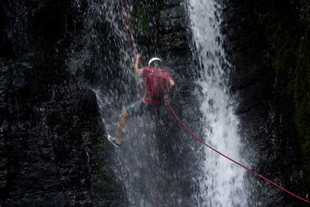 ZAMORA REGION, YANTZAZA, ECUADOR-May 11:Rappel student climbs down waterfall  in Yantzaza, Ecuador on May 11, 2013. Rappelling is part of a tourism class.