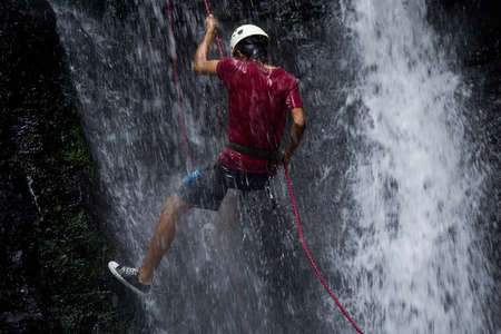 ZAMORA REGION, YANTZAZA, ECUADOR-May 11:Rappel student climbs down waterfall  in Yantzaza, Ecuador on May 11, 2013. Rappelling is part of a tourism class. Editorial