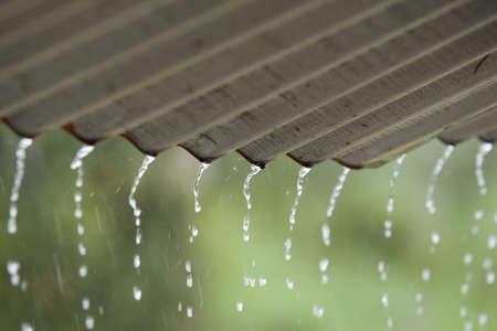 Streams esővíz öntsük le a pótolva tető, szürke tető, zöld háttér szelektív összpontosít