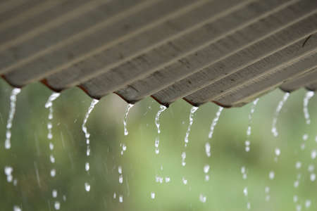 Streams of rain water pour off a corrigated roof, grey roof, green background selective focus Stock Photo