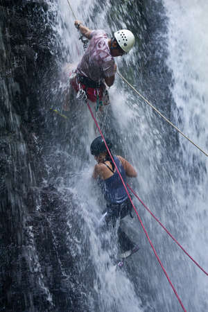 ZAMORA REGION, YANTZAZA, ECUADOR-May 19:Rappel student climbs down waterfall guided by instructors in Yantzaza, Ecuador on May 11, 2013. Rappelling is part of a tourism class.