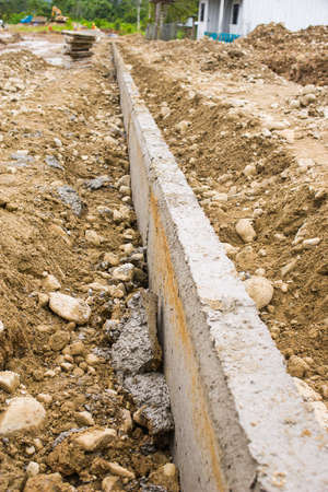 New concrete curb installed in dirt and rocks on new street Stock Photo
