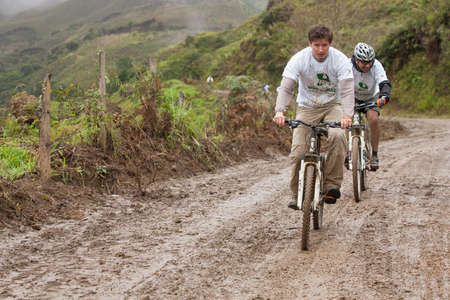 ZAMORA REGION, ECUADOR-July  13 2013:Riders Victor Gravot and Fernando Ortega Aguirre in the rain and mud in the Andes Mountains on July 13, 2013. Governments in Ecuador are actively promoting fitness activities.