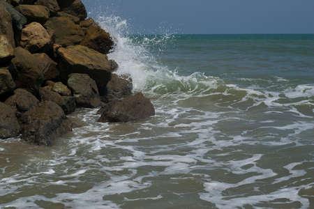 Waves smashing over rocks in sunny sea shore Stock Photo