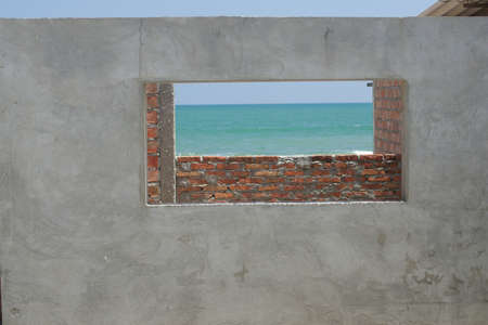 Brick and concrete building under constuction with view of water and waves