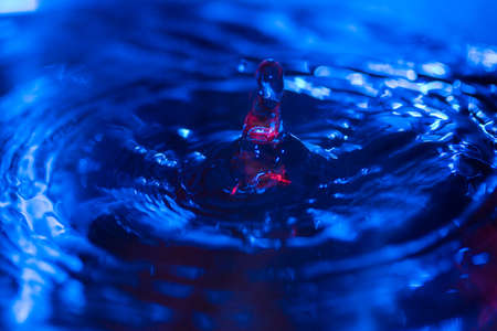 water drops falling on water with blue lights abstract emotion turmoil