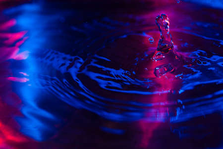 Water drops falling on water with color blue and magenta lights abstract