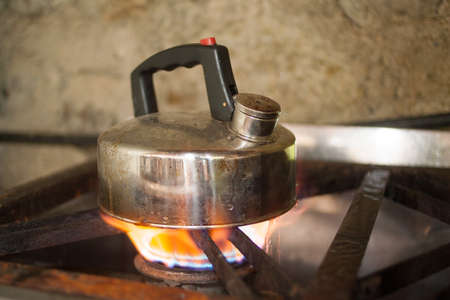 kettle on gas flame cooker large flame photo