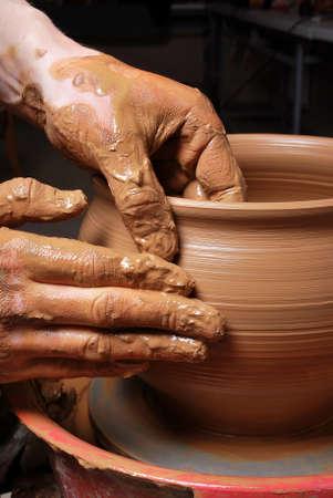 alfarero: manos de un alfarero, creando una vasija de barro en el círculo