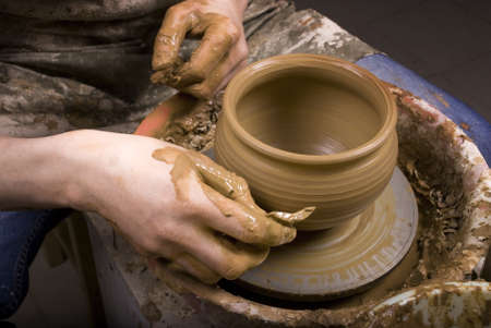 The hands of a potter, creating an earthen jar on the circle, close-up