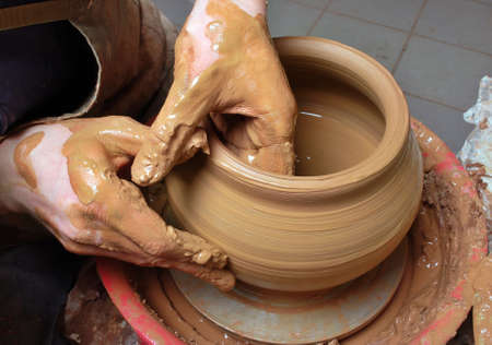 hands of a potter, creating an earthen jar on the circle Stock Photo - 11549199