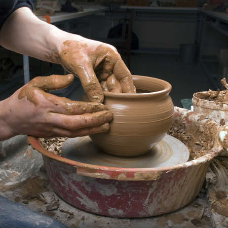 The hands of a potter, creating an earthen jar on the circle, close-ups photo