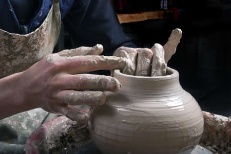 Potter at work creating clay bowl on turning wheel