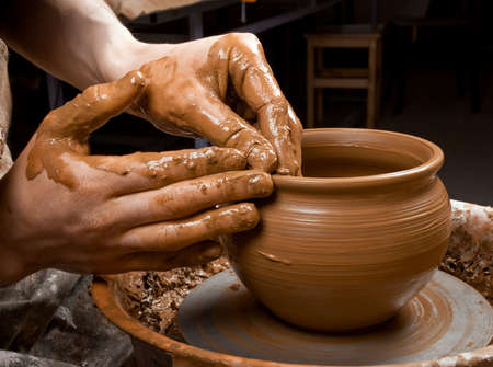 ollas de barro: manos de un alfarero, la creaci�n de una vasija de barro en el c�rculo Foto de archivo
