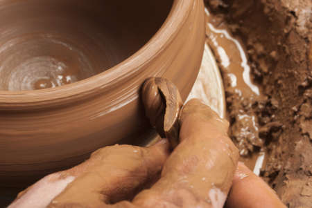 hands of a potter, creating an earthen jar on the circle