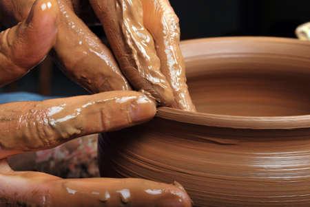 earthen: mani di un vasaio, creando un vaso di terracotta sul cerchio