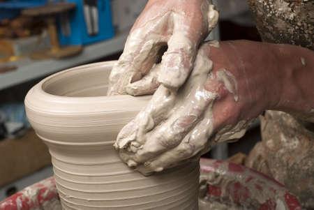 manos sucias: manos de un alfarero, la creación de una vasija de barro en el círculo Foto de archivo