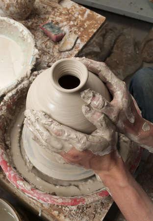 manos sucias: manos de un alfarero, creando una vasija de barro en el círculo