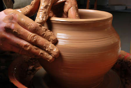 clay pot: hands of a potter, creating an earthen jar on the circle