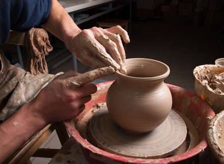 hands of a potter, creating an earthen jar on the circle Stock Photo - 13183751